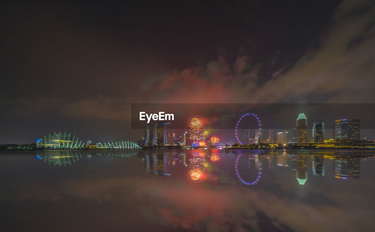 Marina Bay Sands And Ferris Wheel Reflecting On Bay Of Water In City At Night