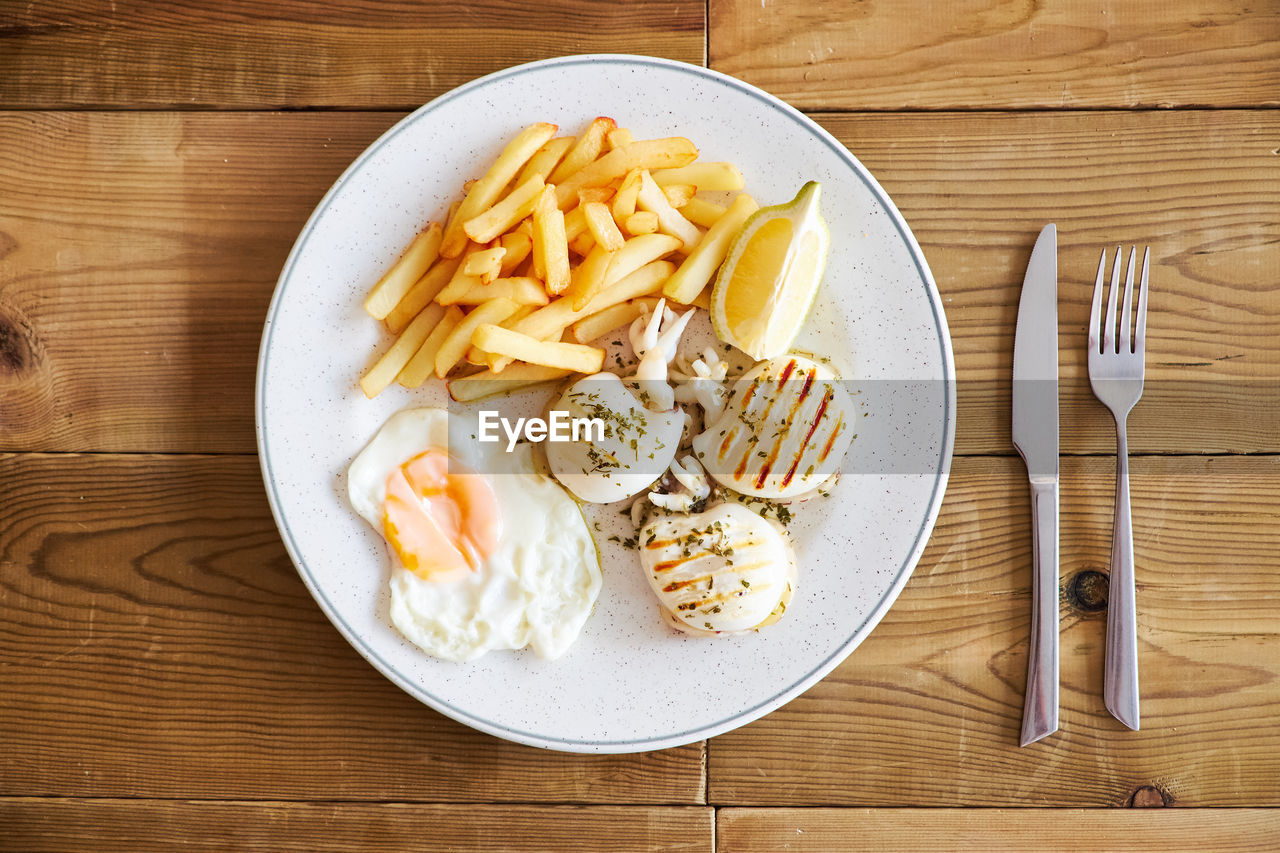 food, food and drink, kitchen utensil, eating utensil, directly above, ready-to-eat, fork, table, freshness, indoors, healthy eating, plate, pasta, high angle view, italian food, wellbeing, potato, no people, wood - material, still life, meal, table knife, fried, breakfast, garnish, temptation, snack