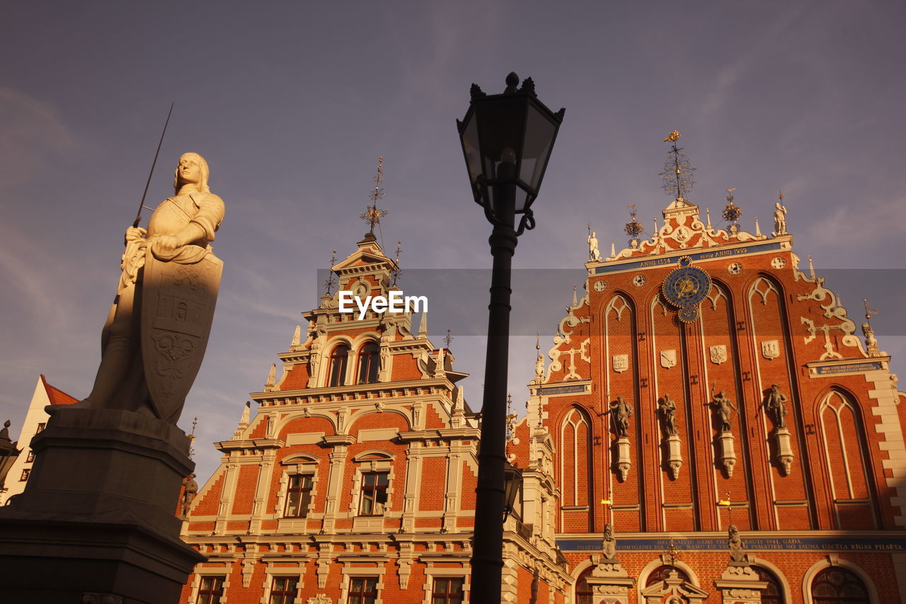 Low Angle View Of Statue And Buildings Against Sky On Sunny Day