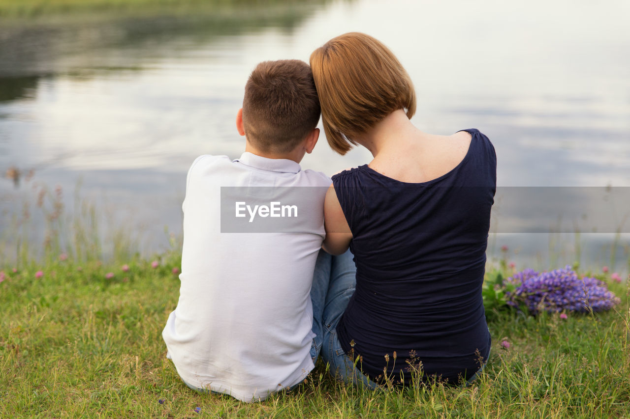 Rear view of brother and sister sitting at lake