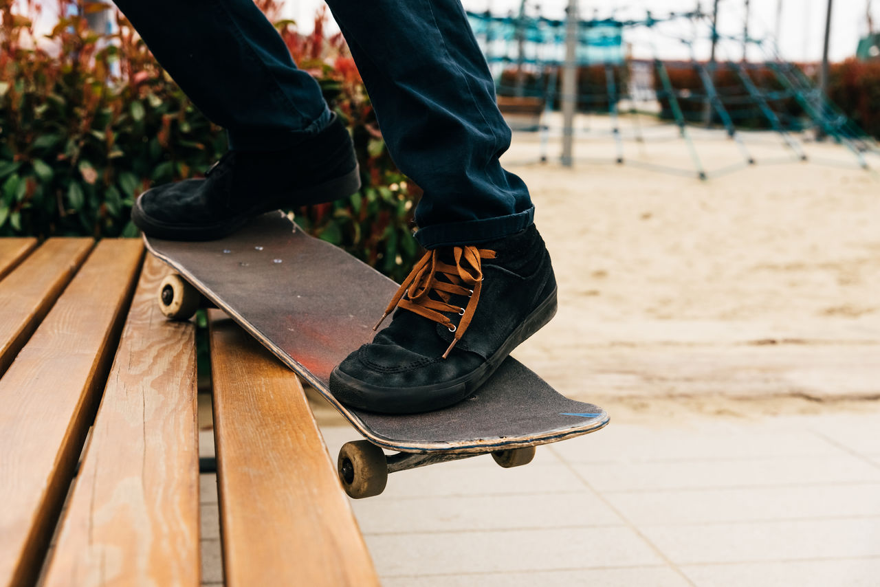 low section, one person, real people, shoe, human leg, lifestyles, human body part, body part, leisure activity, day, focus on foreground, standing, men, outdoors, sport, wood - material, unrecognizable person, casual clothing, nature, human foot, jeans