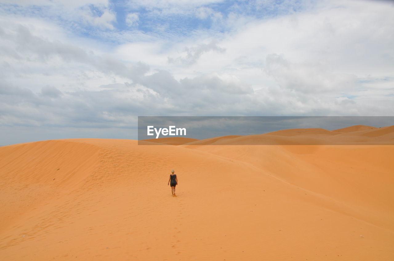Scenic View Of Woman Walking In Desert Against Sky