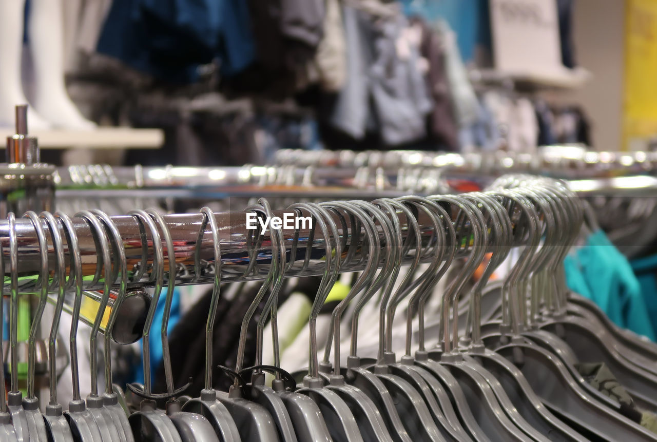 Close-up of coathangers hanging on rack in store