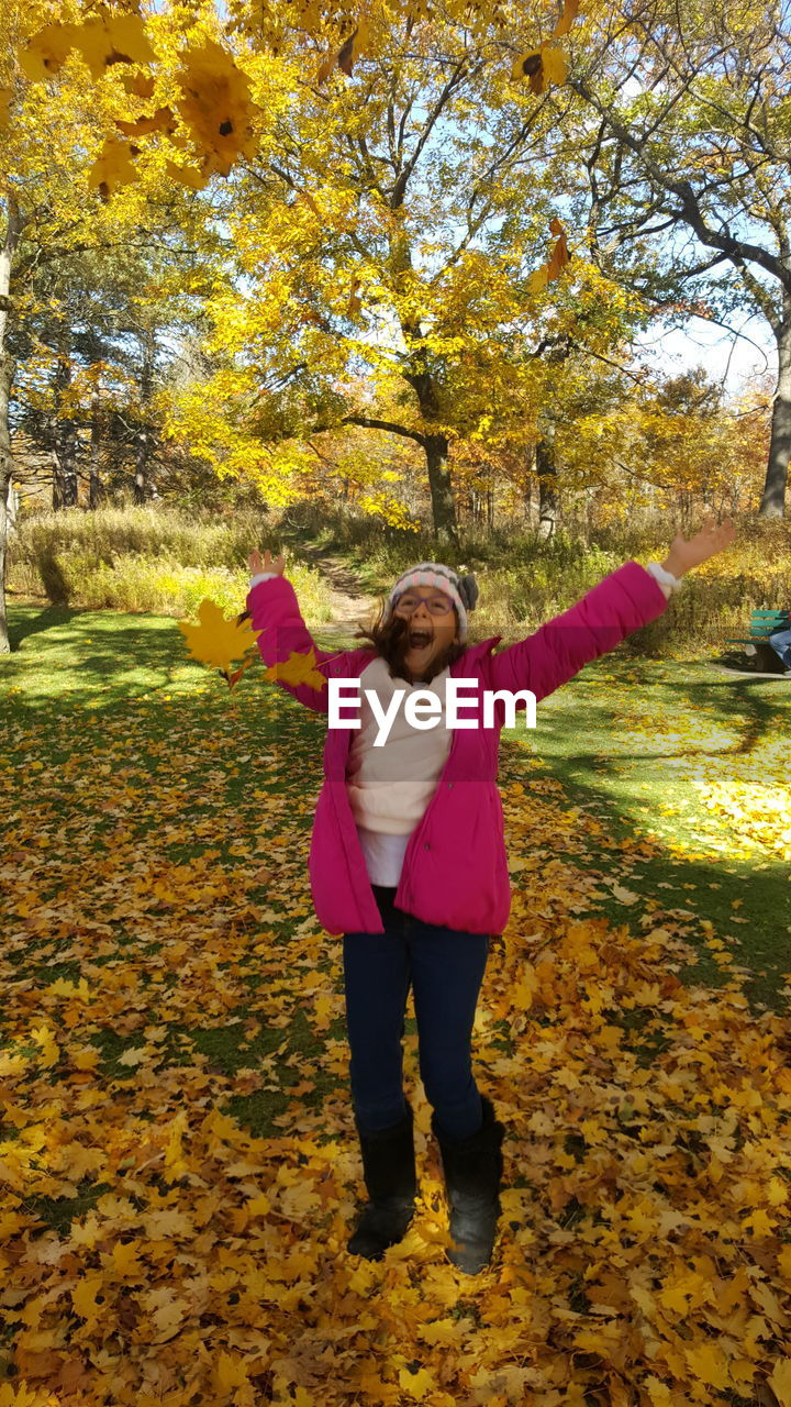 autumn, tree, one person, full length, front view, plant, change, leaf, leisure activity, nature, plant part, casual clothing, women, human arm, yellow, day, real people, lifestyles, standing, arms outstretched, limb, outdoors, warm clothing, arms raised, human limb, hairstyle