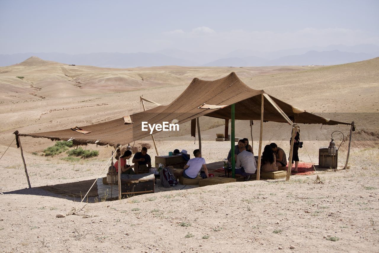 group of people, land, sky, real people, nature, sand, leisure activity, men, day, landscape, lifestyles, desert, people, architecture, environment, adult, women, mountain, sunlight, outdoors, arid climate, climate