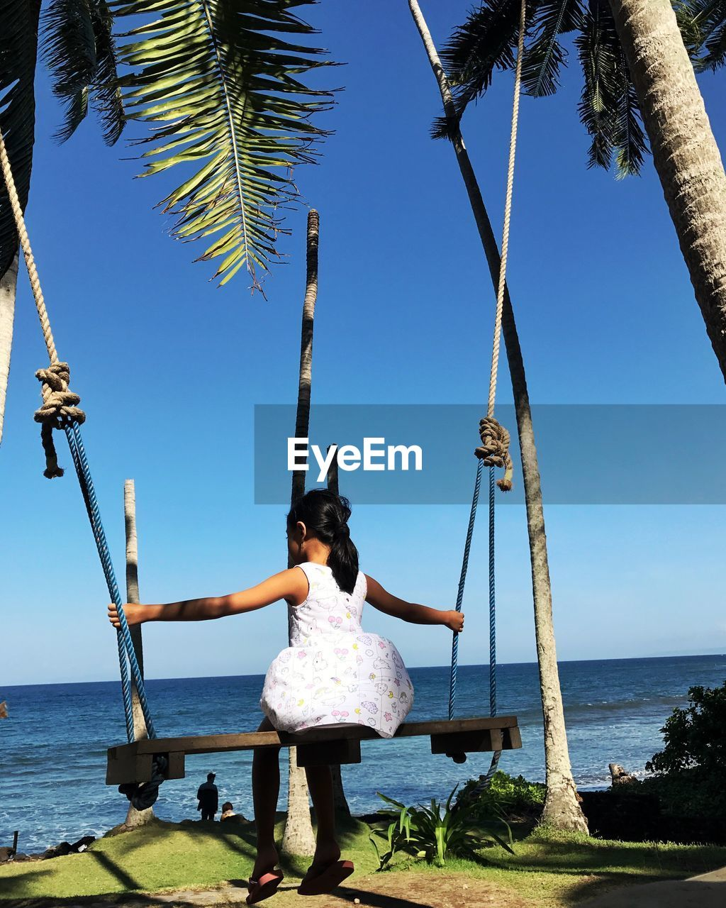 Girl Sitting On Swing At Beach Against Sky