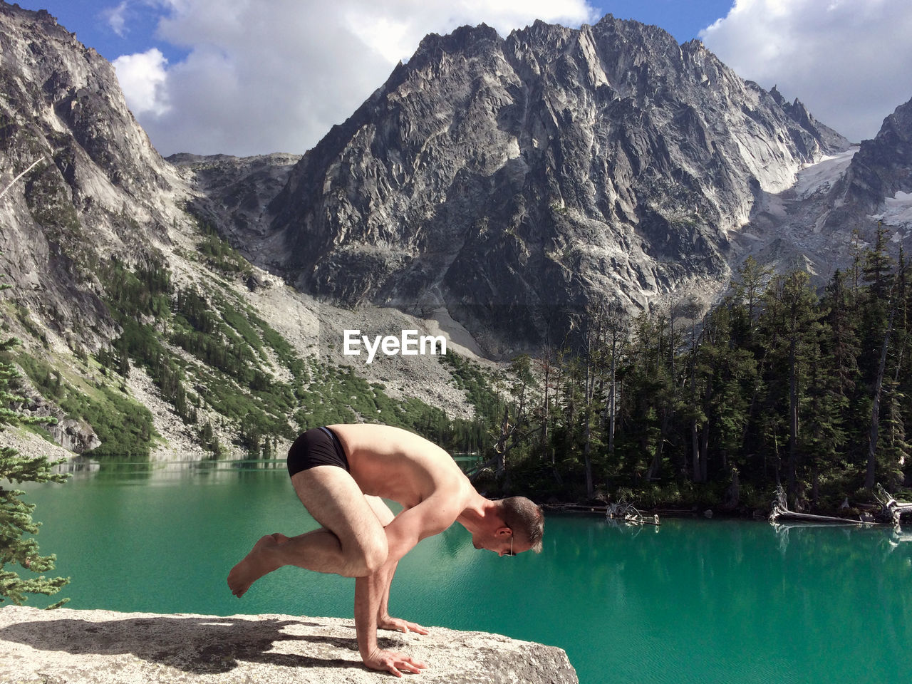 Side View Of Shirtless Man Practicing Yoga On Rock Against Dragontail Peak