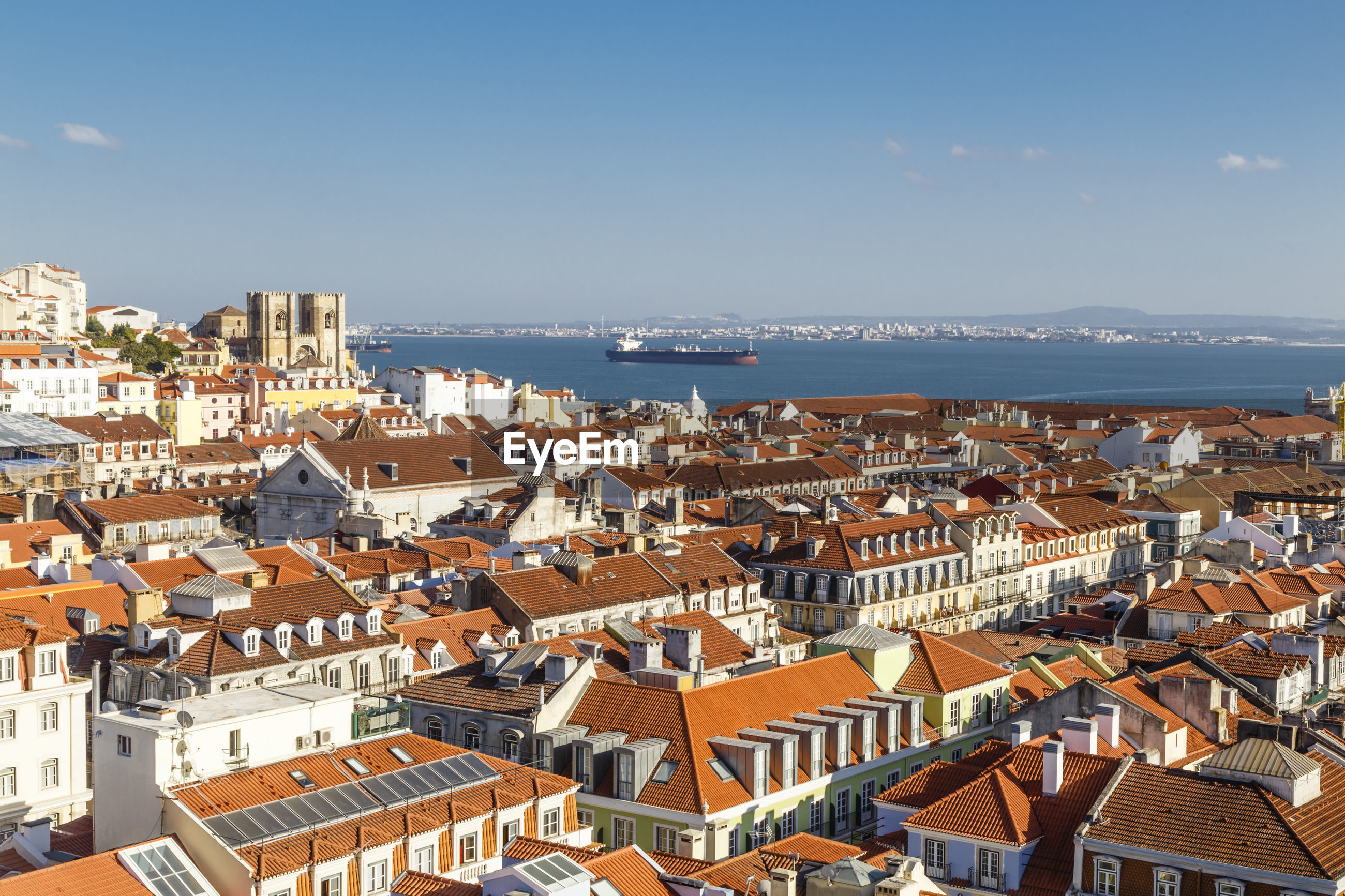 HIGH ANGLE VIEW OF CITYSCAPE AGAINST SEA