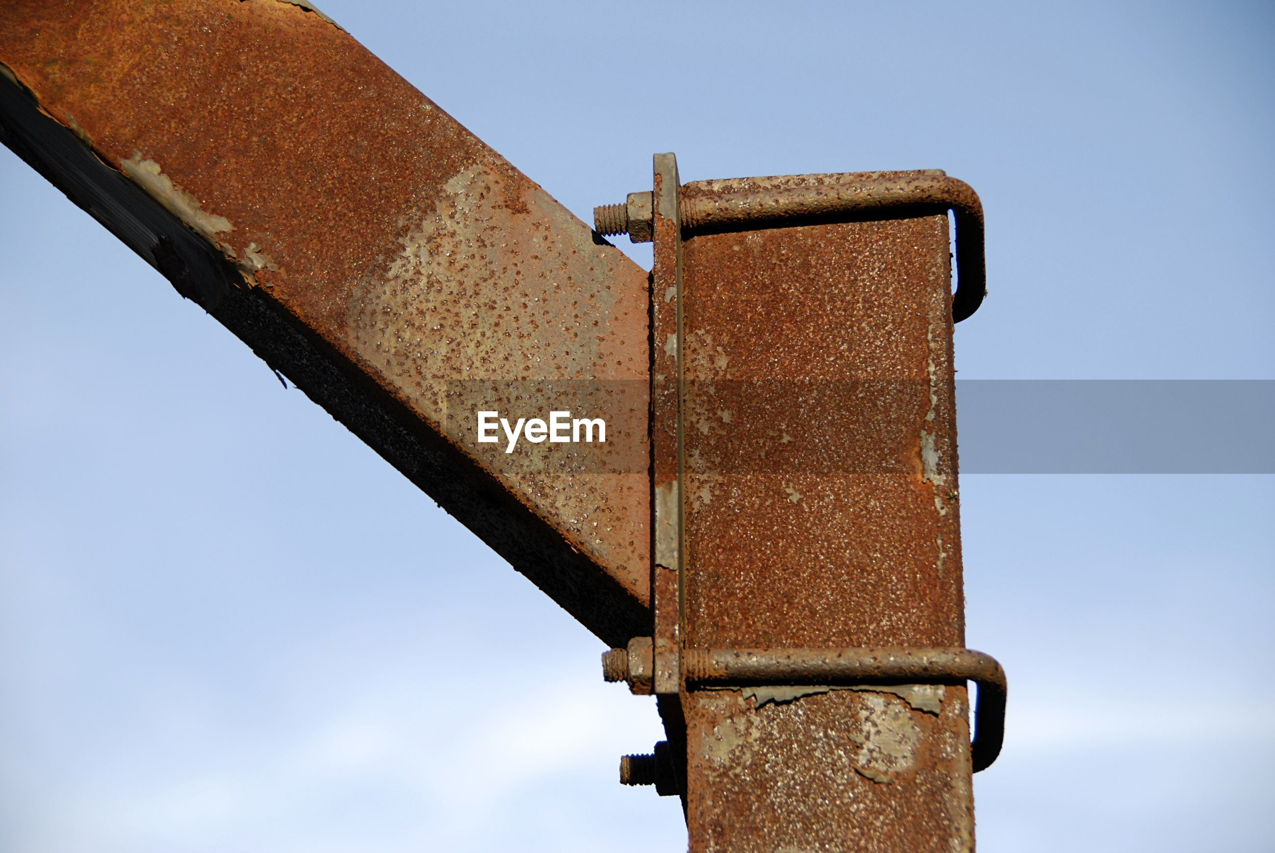 Low angle view of rusty metal against sky