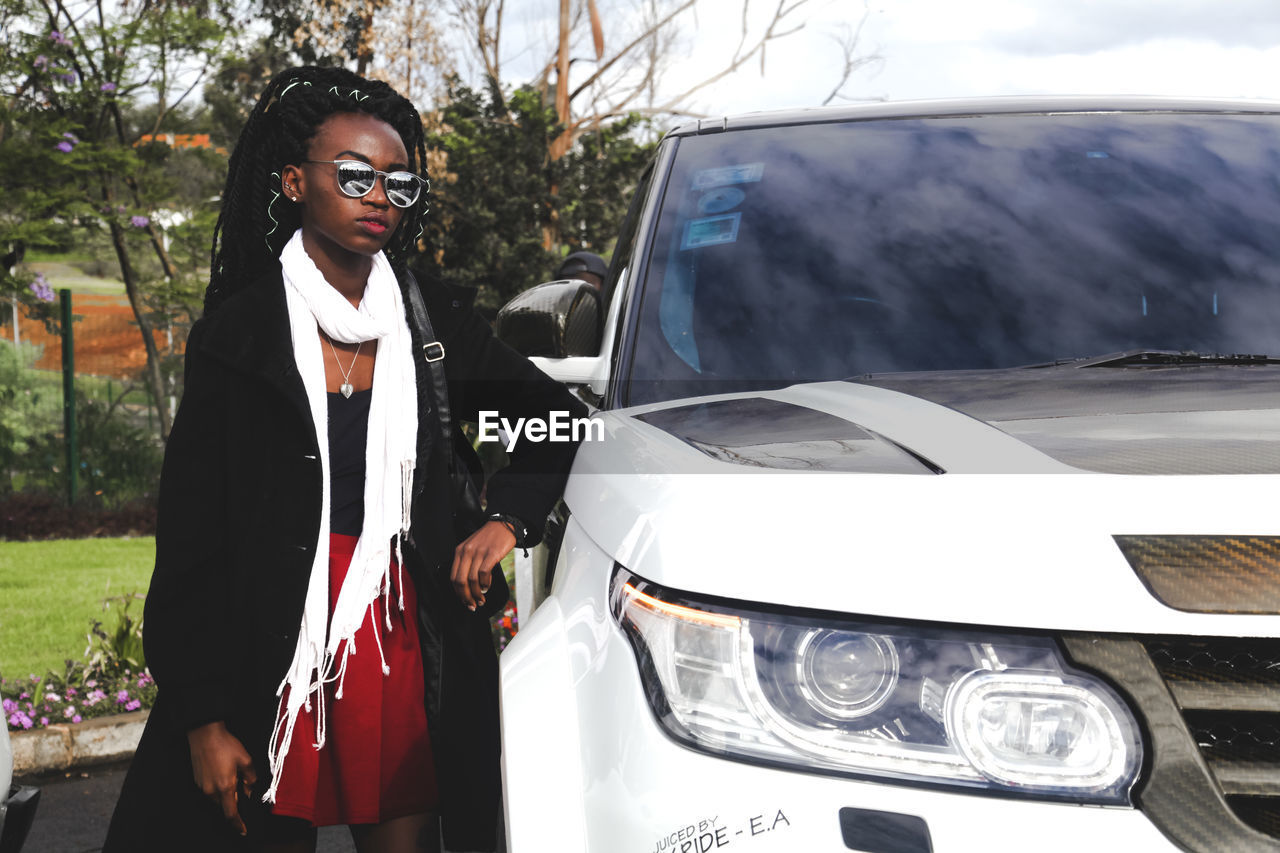 Young Woman Wearing Sunglasses Standing By Car
