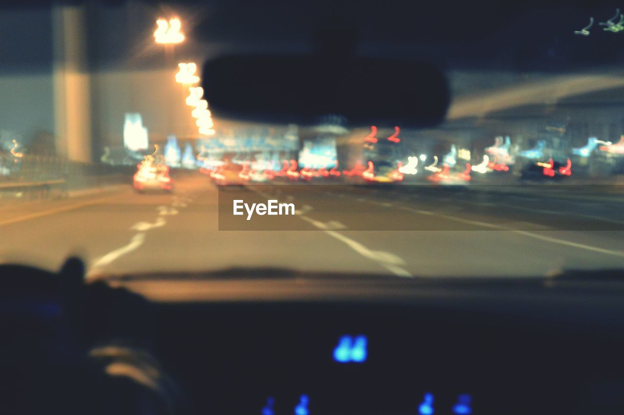 car, transportation, road, land vehicle, windshield, car interior, vehicle interior, illuminated, car point of view, night, street, traffic, the way forward, highway, mode of transport, driving, no people, dashboard, speedometer, outdoors, city, close-up