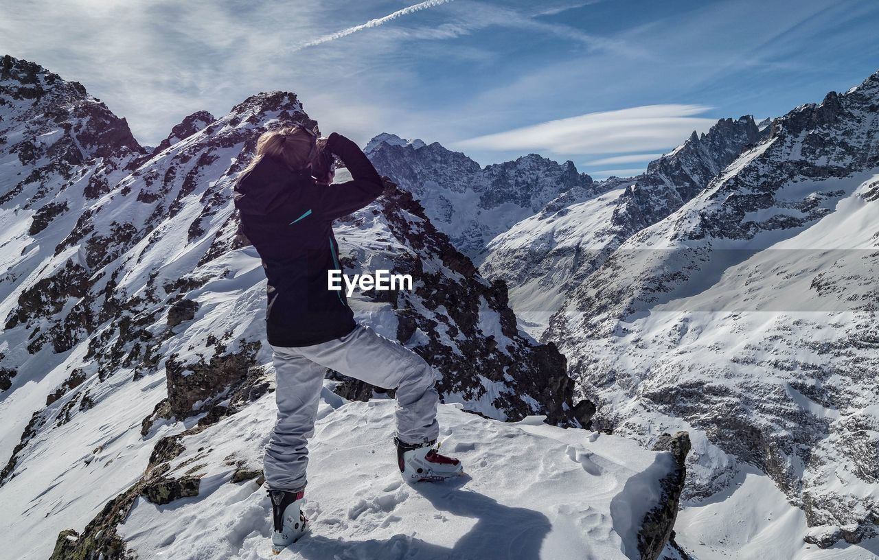 Side view of woman standing on snowcapped mountain