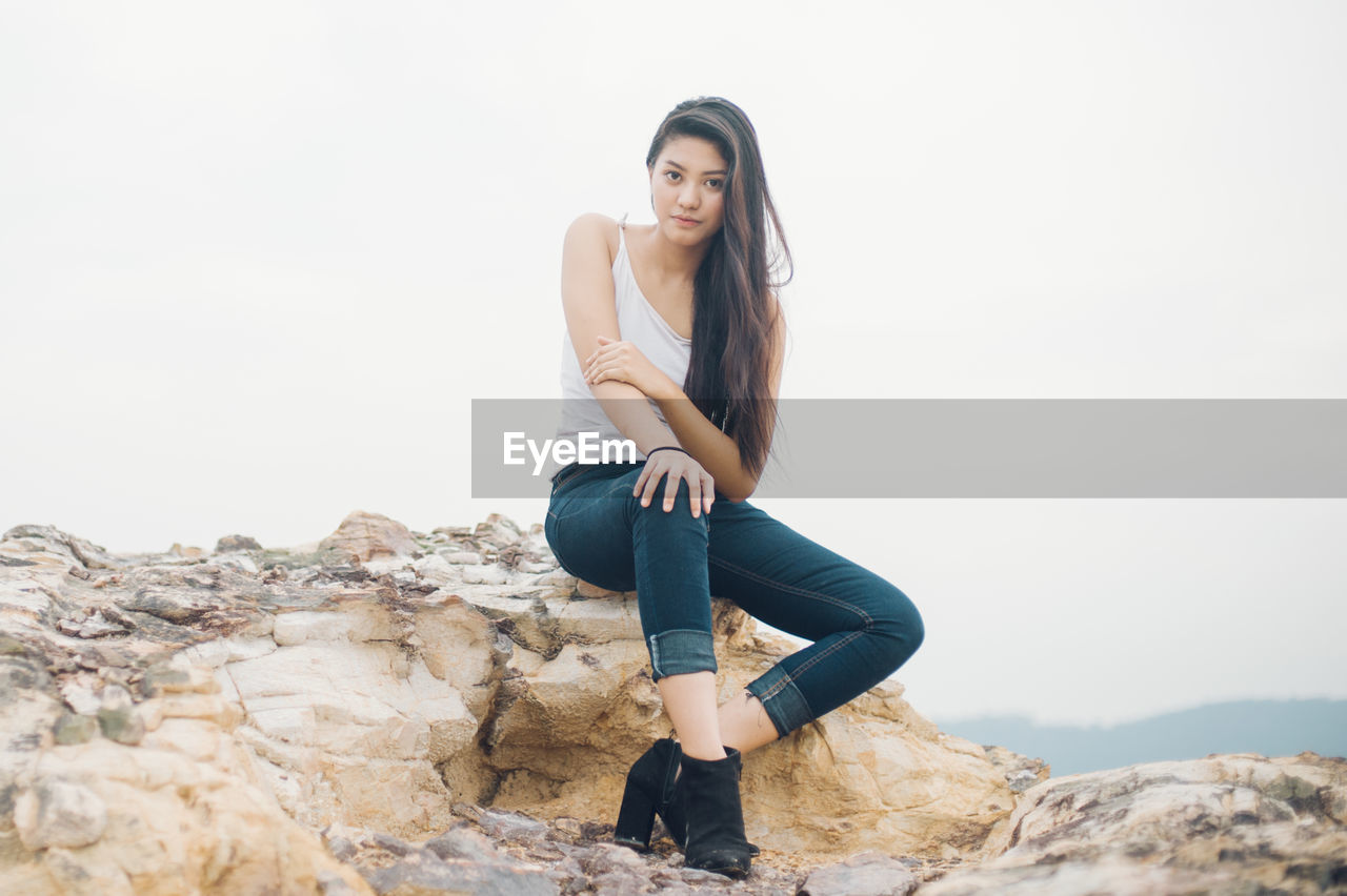 Portrait of beautiful fashion model sitting on rock formation against clear sky