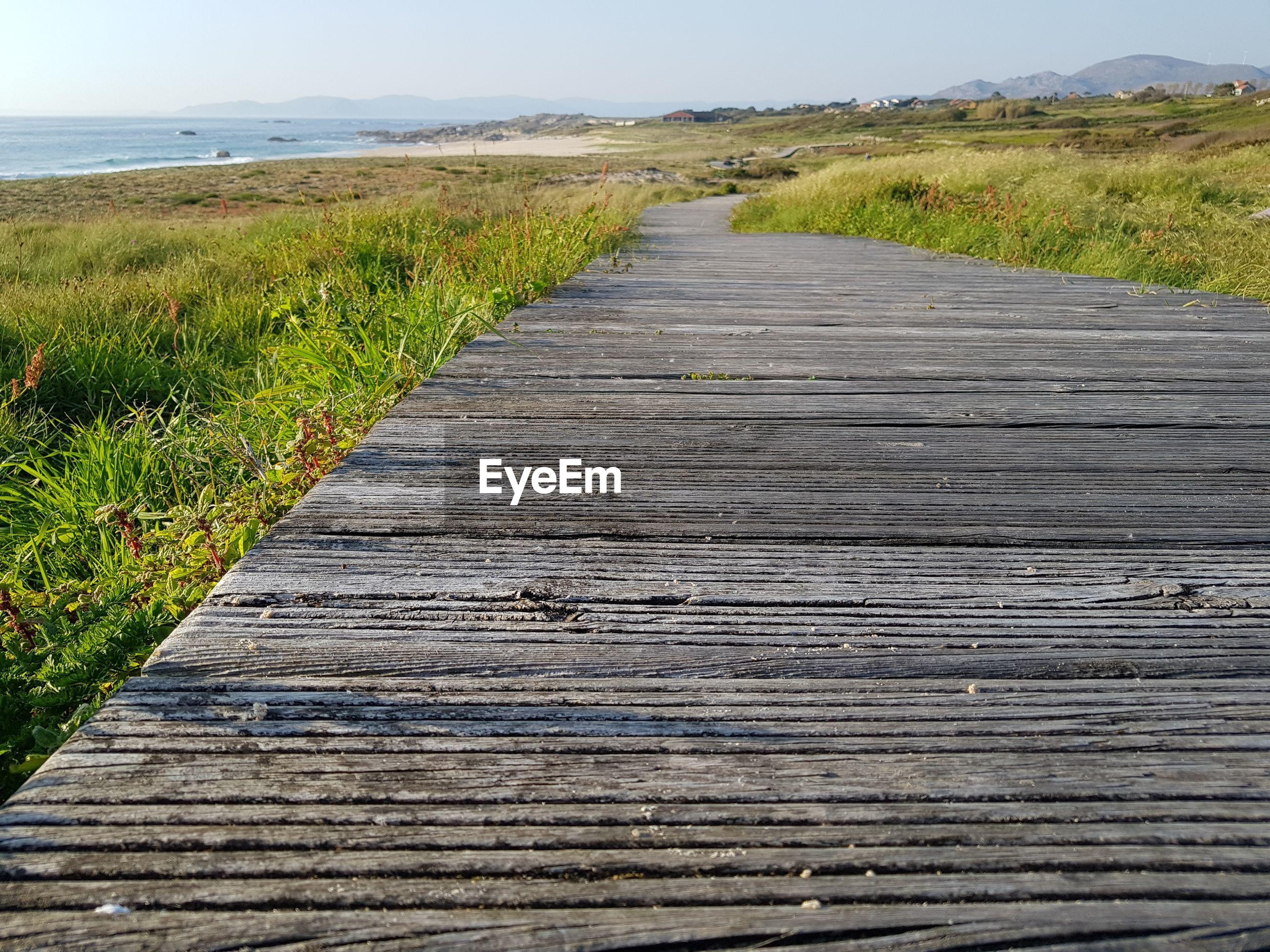 Surface level of boardwalk on landscape against sky