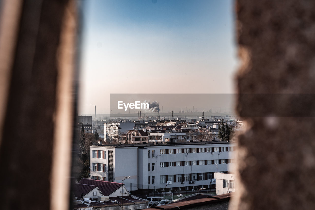 building exterior, built structure, architecture, sky, city, cityscape, focus on background, no people, building, nature, residential district, day, outdoors, high angle view, window, industry, cloud - sky, travel destinations, pollution, settlement