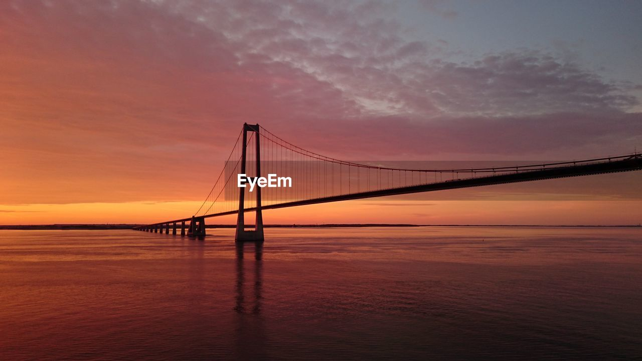 sunset, suspension bridge, water, bridge - man made structure, sea, sky, connection, nature, beauty in nature, scenics, waterfront, built structure, tranquil scene, outdoors, architecture, no people, transportation, bridge, tranquility, travel destinations, cloud - sky, horizon over water