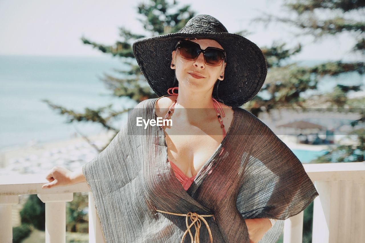 Portrait of woman wearing hat and sunglasses against sea