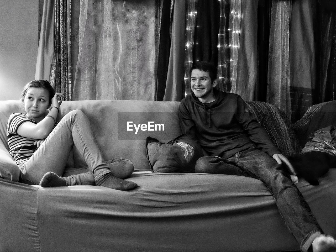 Siblings sitting on sofa at home