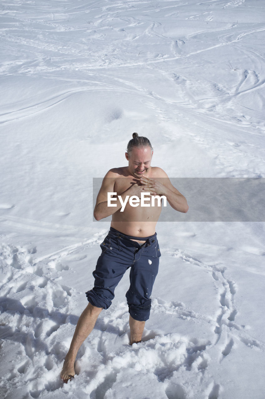HIGH ANGLE VIEW OF SHIRTLESS MAN ON SNOW COVERED FIELD