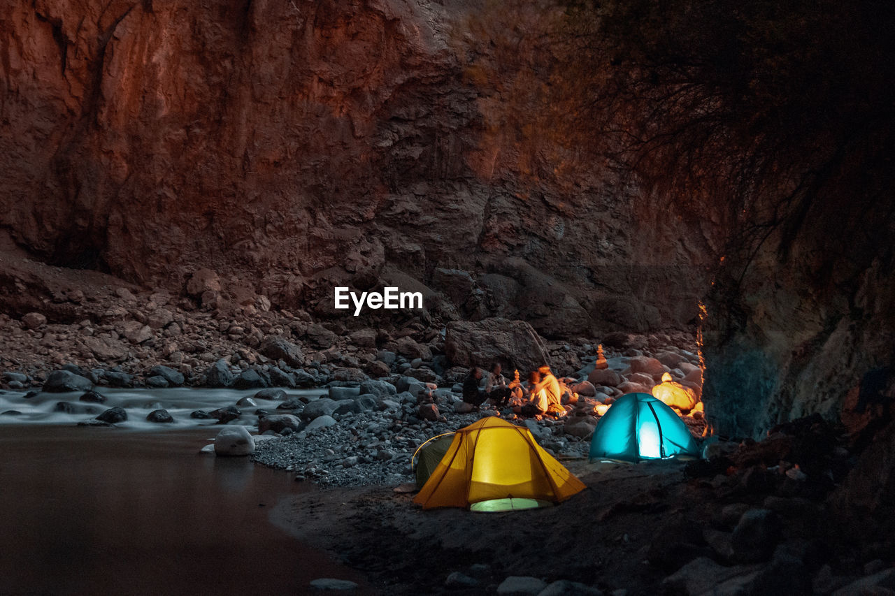 rock, tent, solid, rock - object, camping, water, adventure, rock formation, mountain, nature, beauty in nature, tranquility, no people, cave, outdoors, illuminated, tranquil scene, lighting equipment, scenics - nature