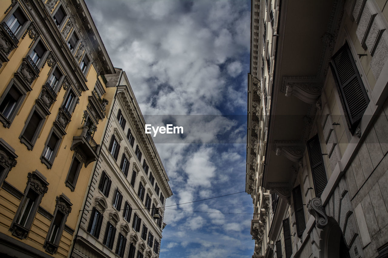 low angle view, building exterior, architecture, cloud - sky, built structure, sky, window, building, no people, residential district, day, nature, city, outdoors, wall - building feature, directly below, the past, history, in a row, apartment