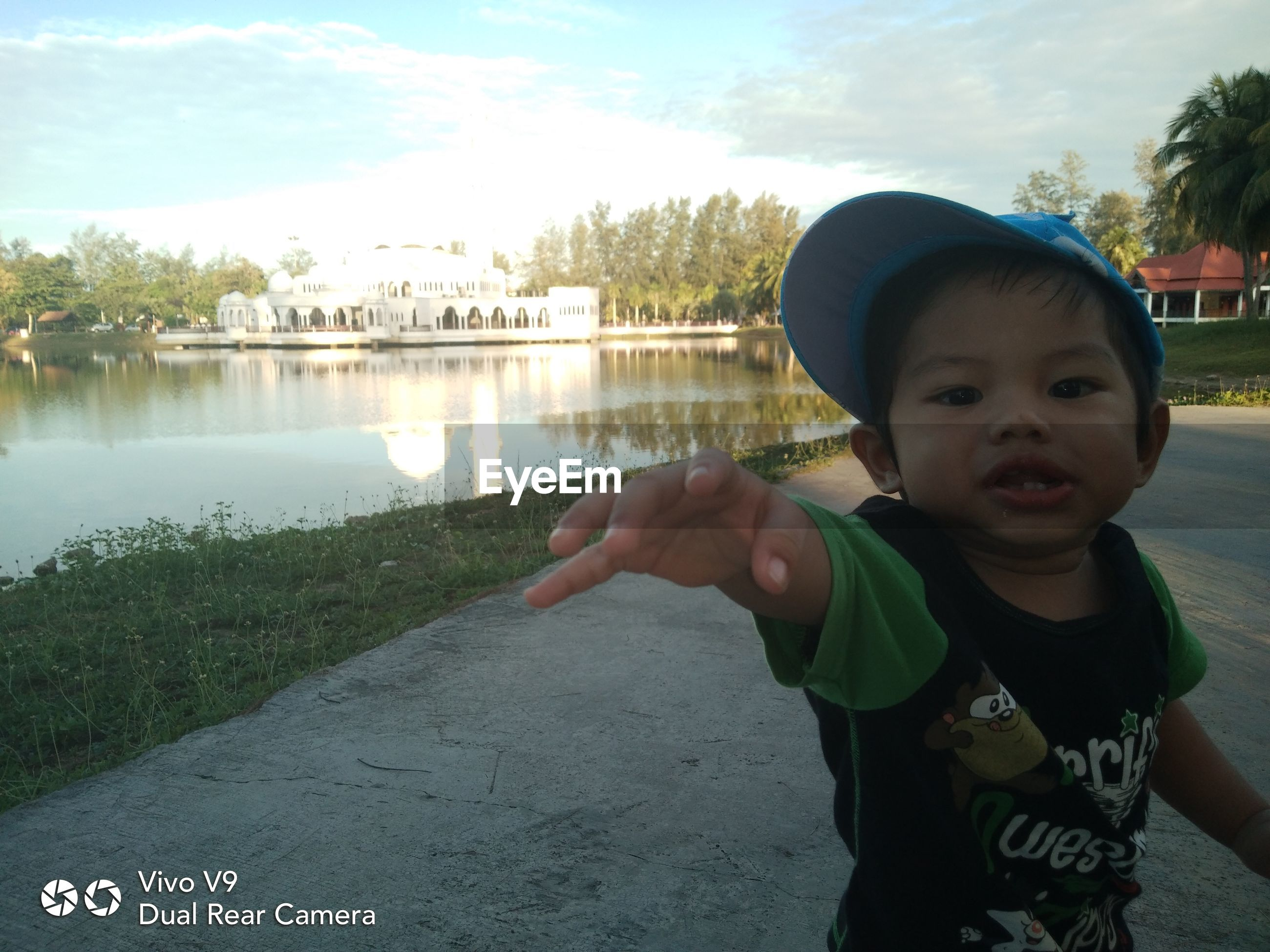 PORTRAIT OF BOY STANDING ON LAKE