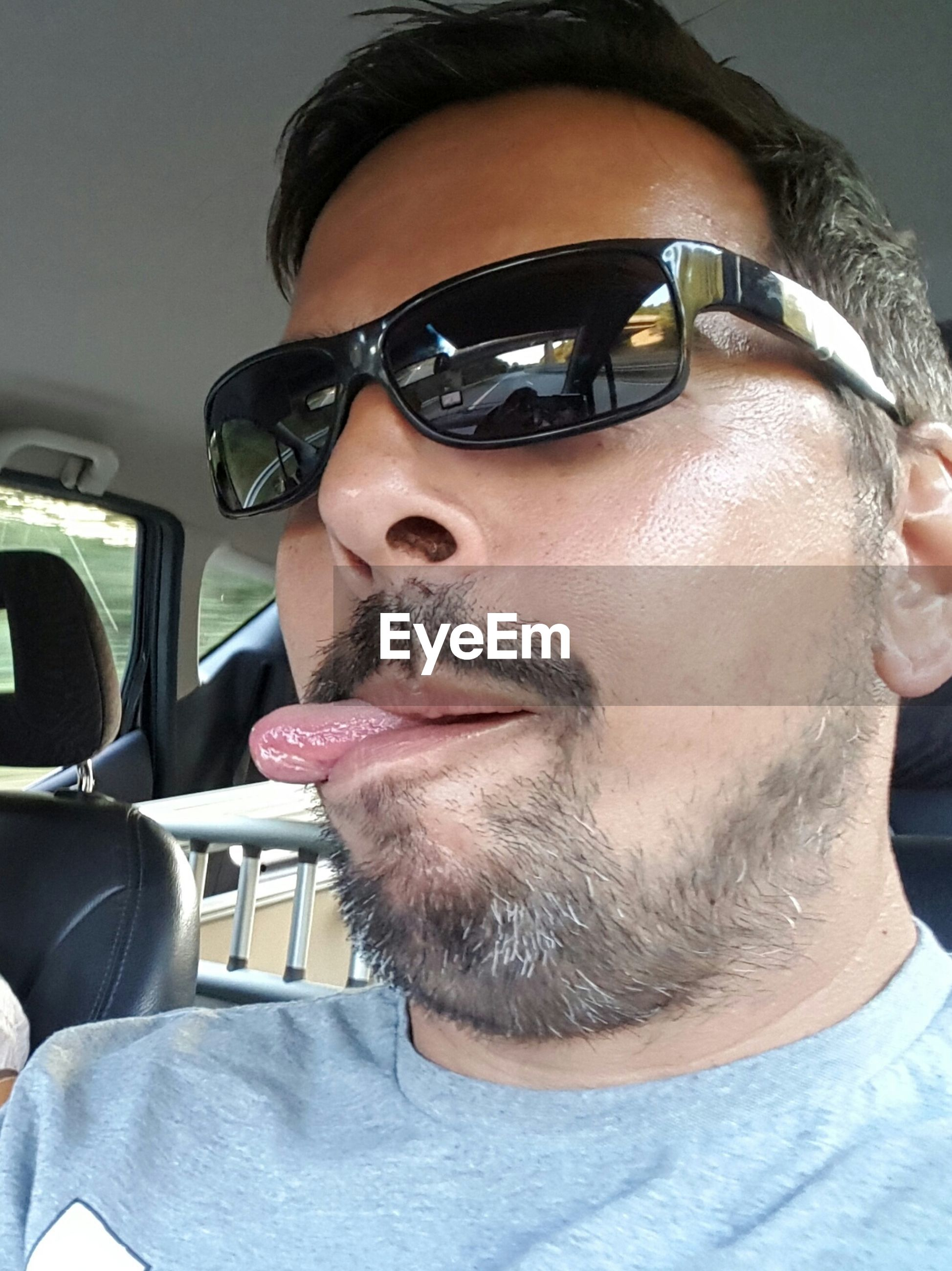 Close-up of man wearing sunglasses sticking out tongue in car