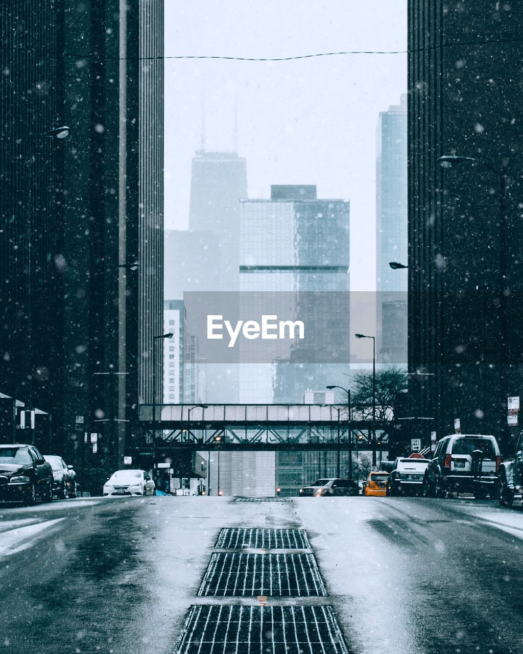 Road amidst buildings in city during snowfall