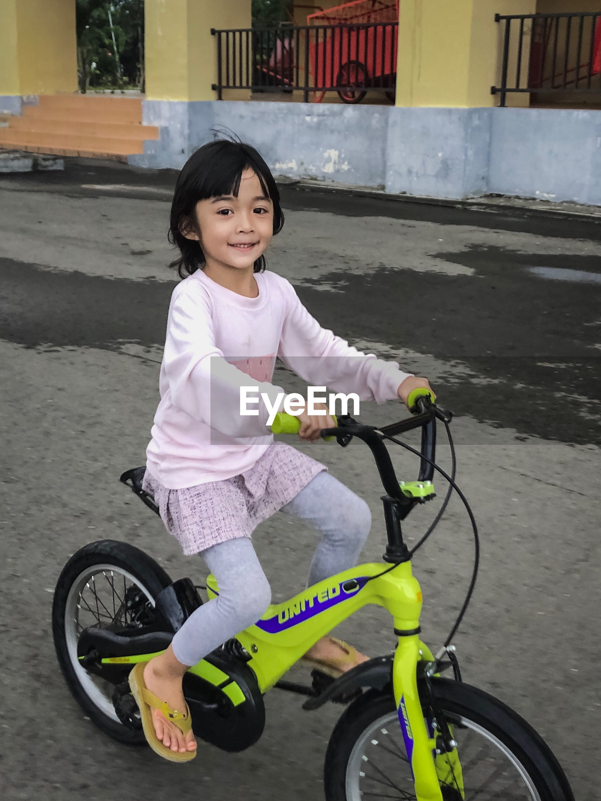 Portrait of cute girl riding bicycle on street