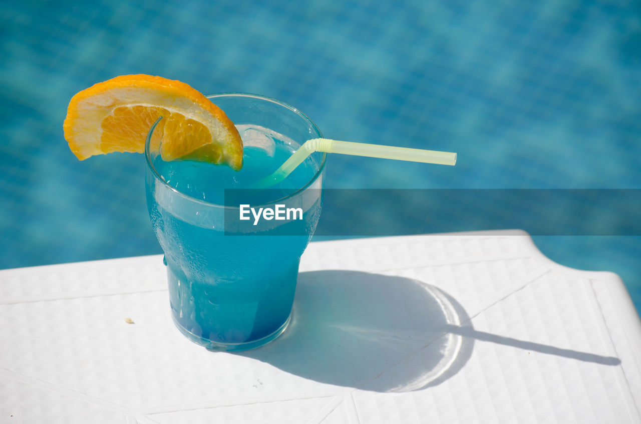 High Angle View Of Fresh Cocktail On Table Against Swimming Pool