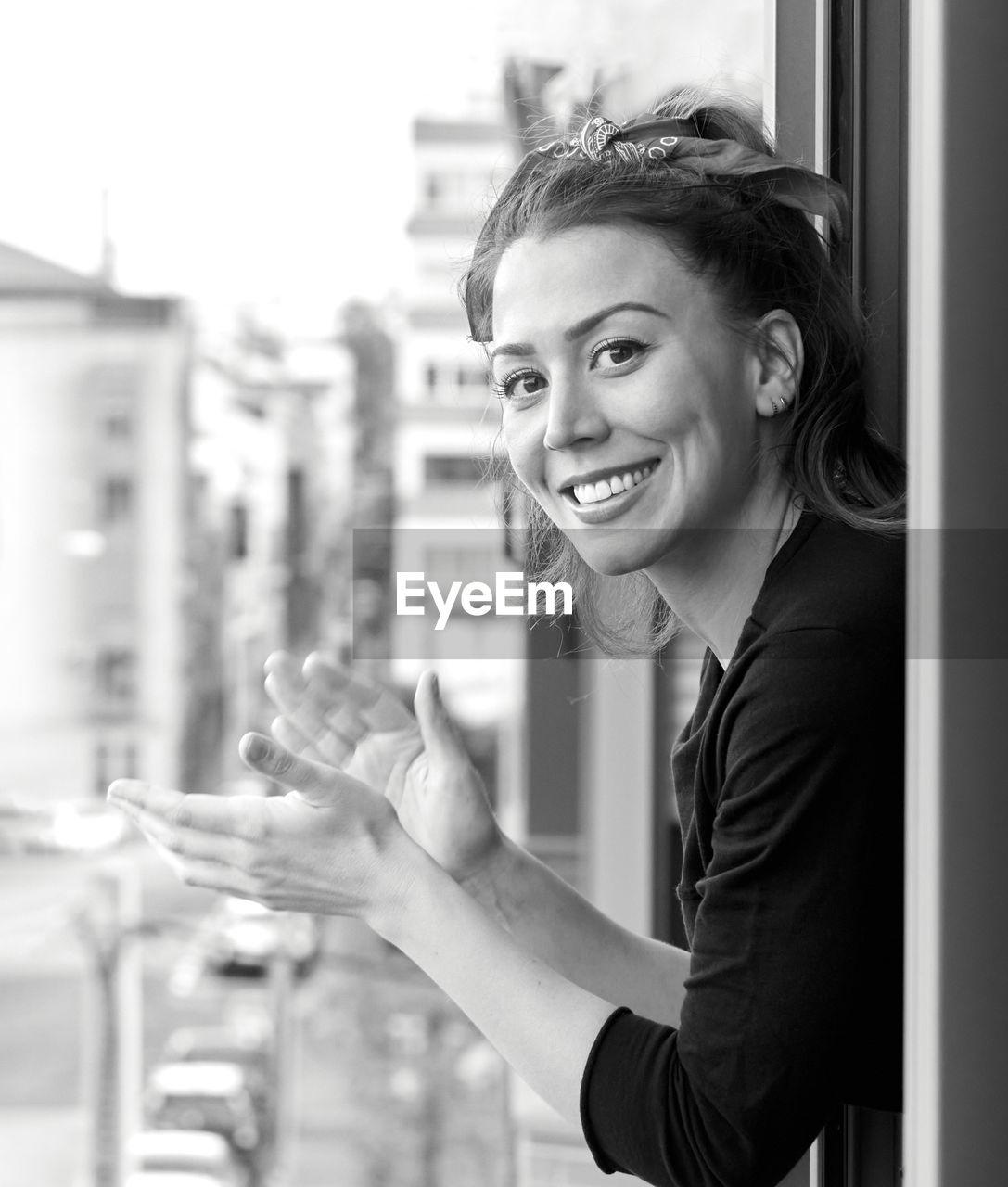 Smiling woman applauding while leaning from window