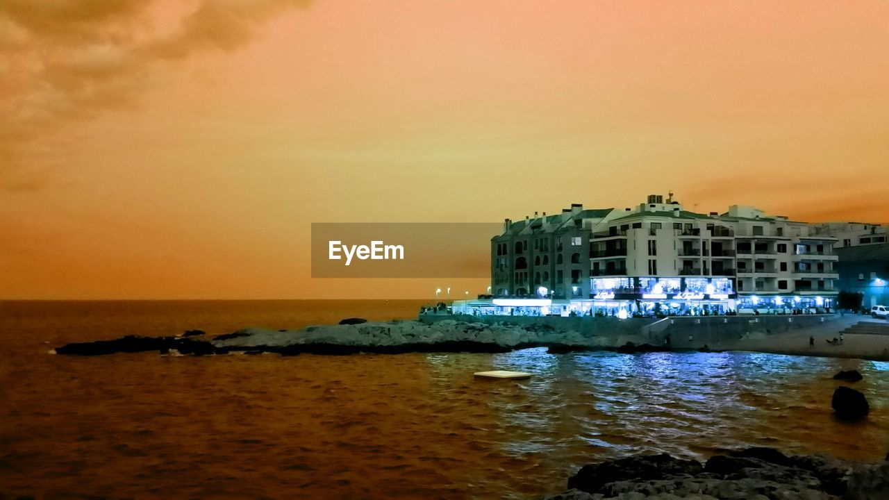 sea, architecture, building exterior, water, sunset, built structure, sky, nature, outdoors, beauty in nature, travel destinations, waterfront, no people, beach, tranquility, scenics, horizon over water, illuminated, night, nautical vessel, city