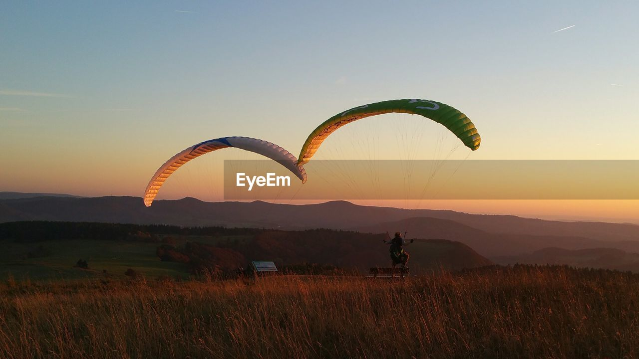 Person paragliding on field against sky during sunset