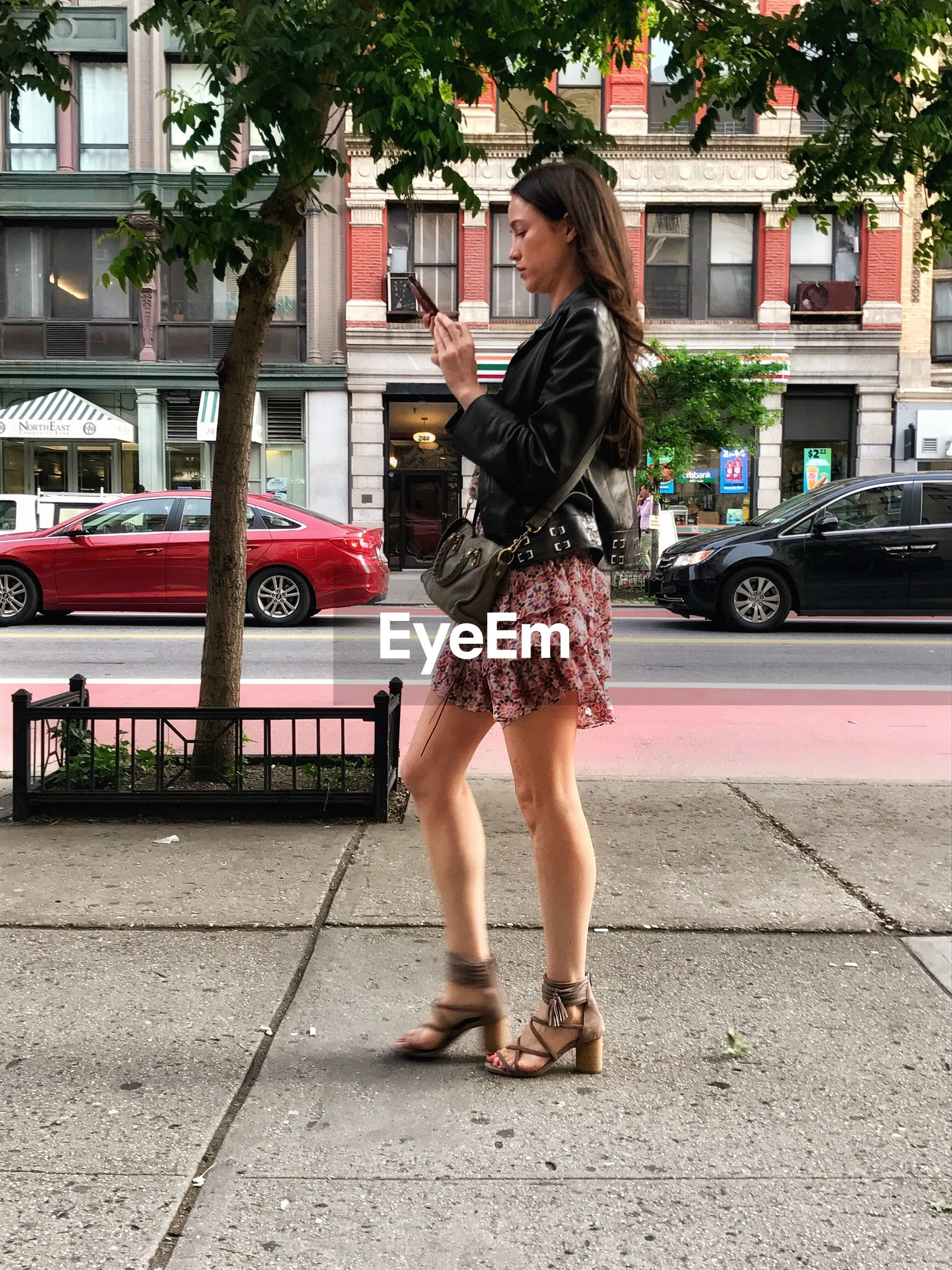 one person, full length, young adult, real people, young women, standing, building exterior, built structure, street, outdoors, lifestyles, casual clothing, leisure activity, architecture, day, car, transportation, side view, beautiful woman, land vehicle, women, city, tree, one young woman only, adult, people