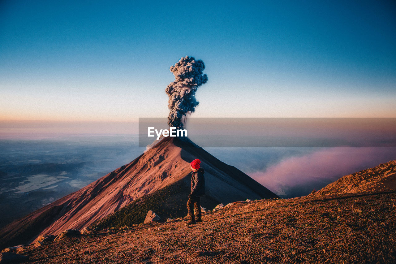 Woman standing against volcanic landscape during sunset