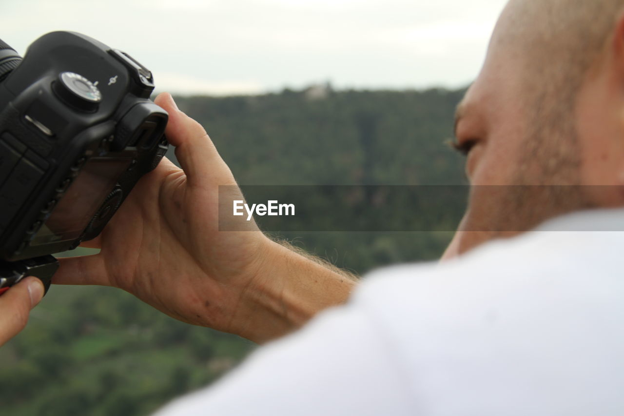 photography themes, camera - photographic equipment, photographing, technology, digital camera, real people, one person, holding, leisure activity, photographer, men, digital single-lens reflex camera, outdoors, camera, close-up, lifestyles, human hand, day, slr camera, nature, sky, people