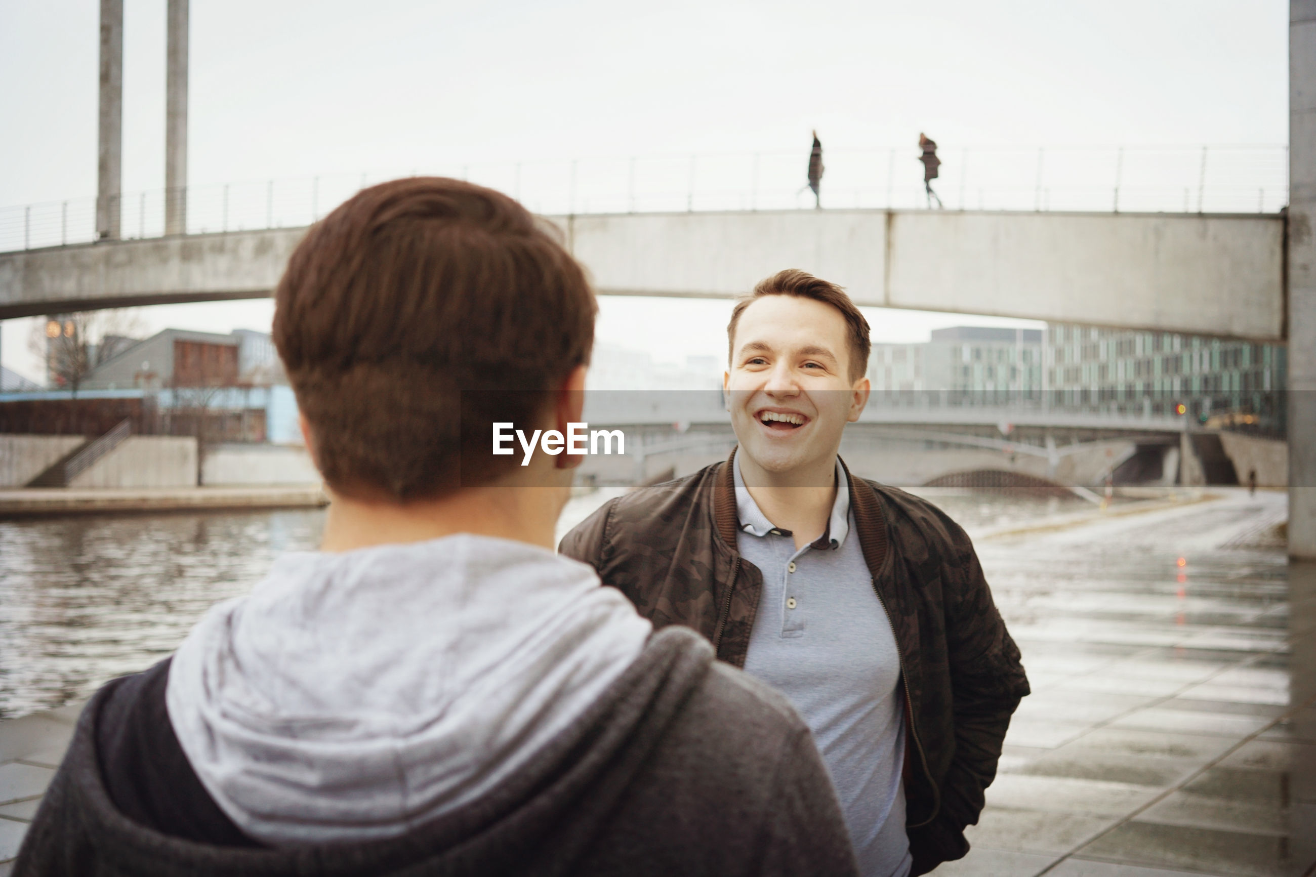 Smiling man talking with friend against bridge in city