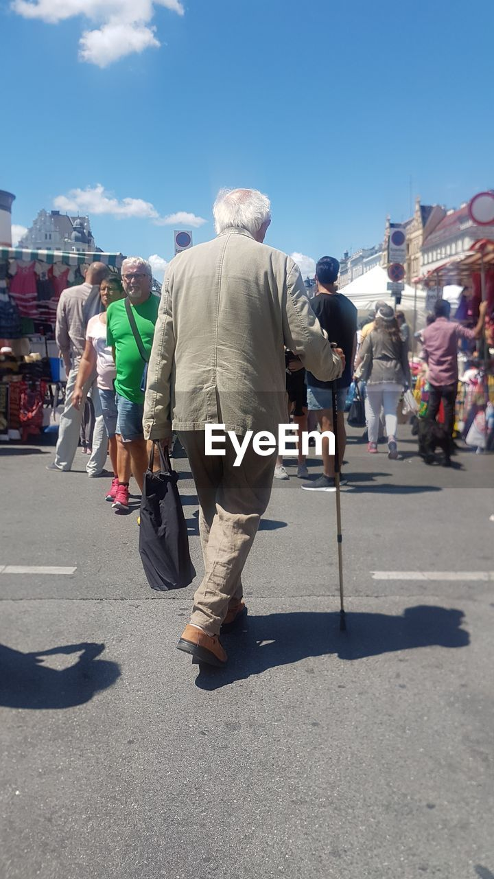 real people, sunlight, senior adult, shadow, walking, large group of people, day, lifestyles, men, senior men, leisure activity, full length, outdoors, casual clothing, senior women, women, crowd, sky, people, adult