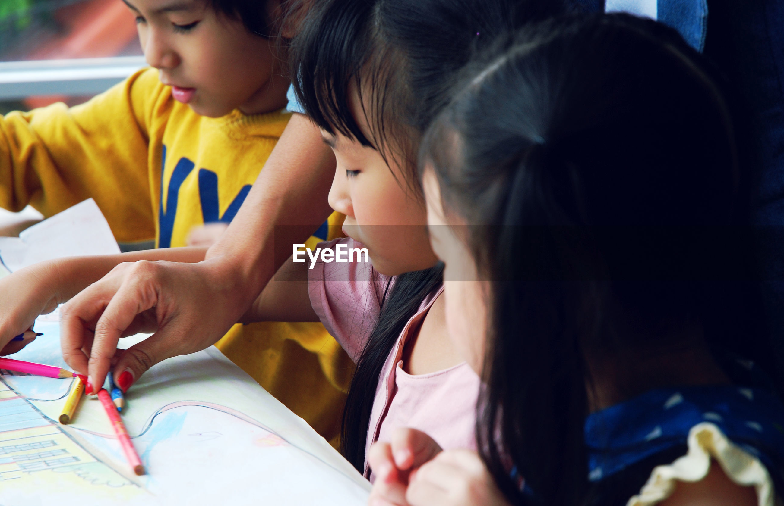 Cropped hand of teacher giving colored pencils to children drawing on paper