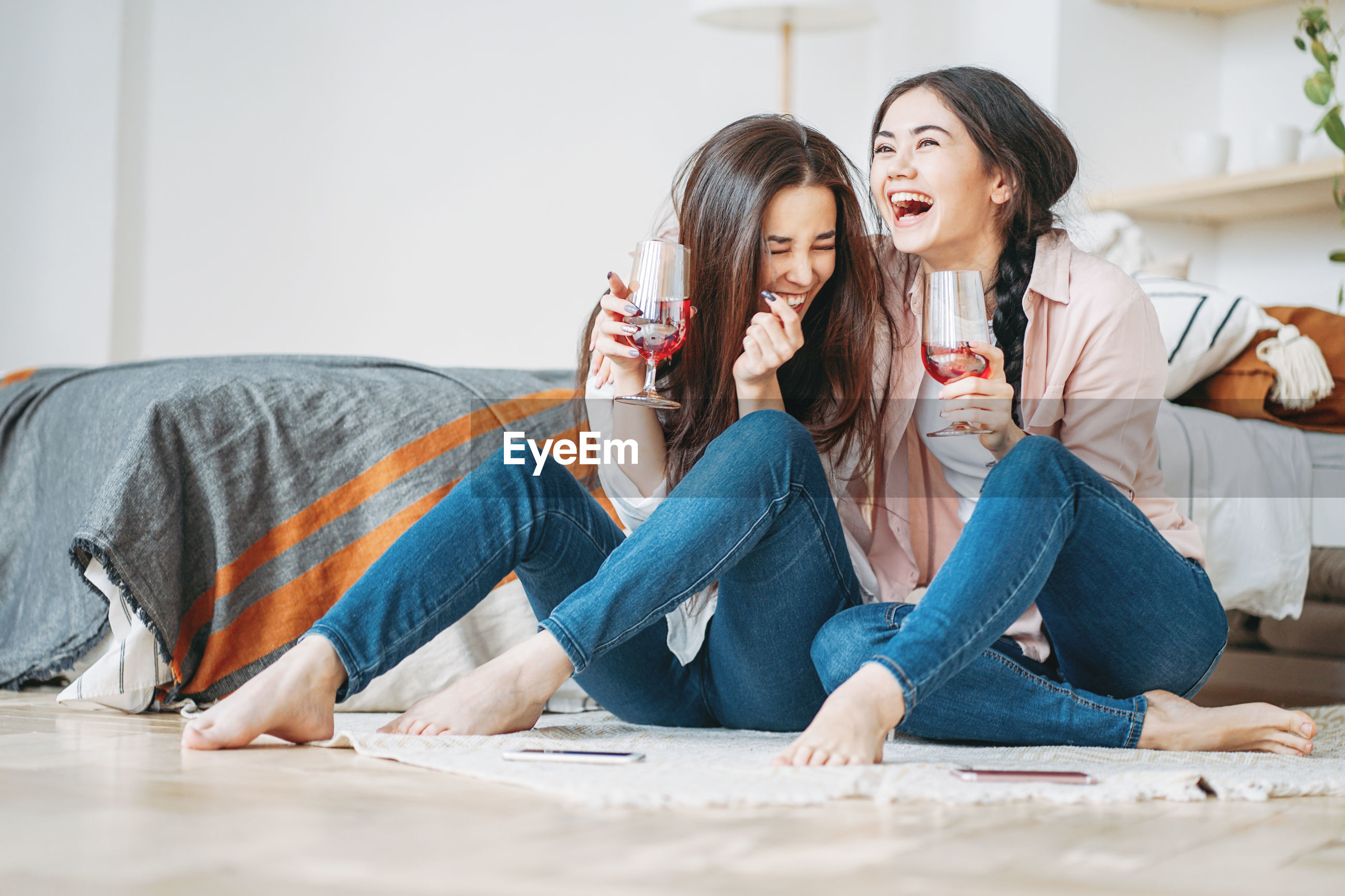 Cheerful female friends having drink while sitting at home
