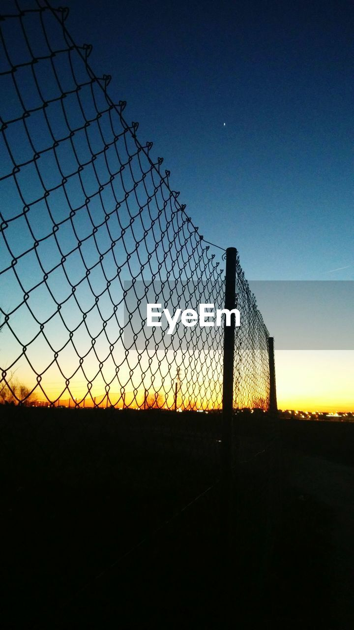 chainlink fence, sky, protection, sport, clear sky, playing field, no people, outdoors, sunset, nature, team sport, beach volleyball, soccer field, goal post, day