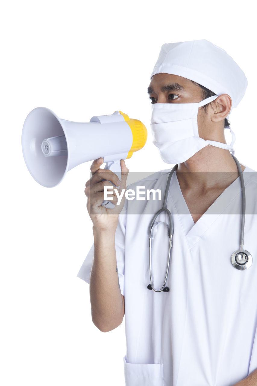 Doctor holding megaphone against white background