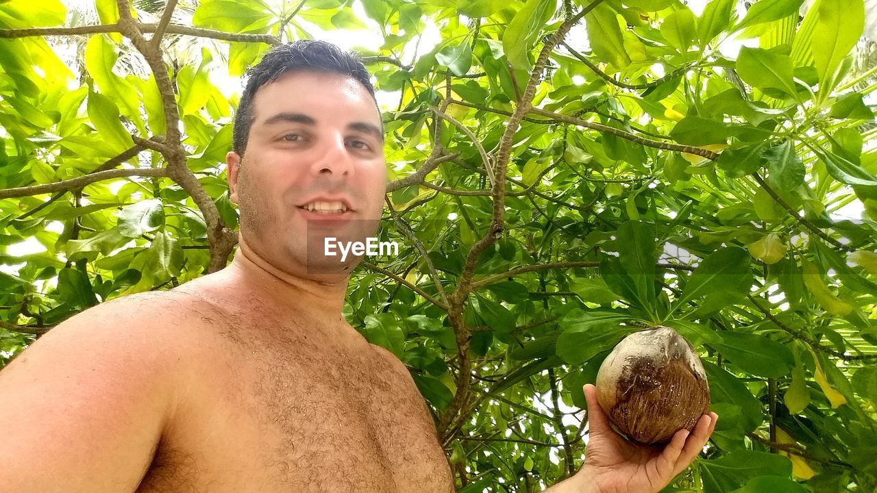 one person, portrait, plant, shirtless, growth, adult, tree, leaf, nature, plant part, lifestyles, young adult, headshot, looking at camera, leisure activity, day, men, front view, smiling, outdoors