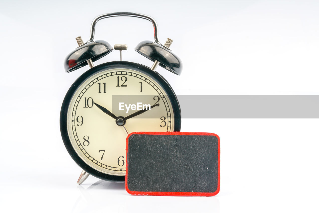 Close-Up Of Clock With Label Over White Background