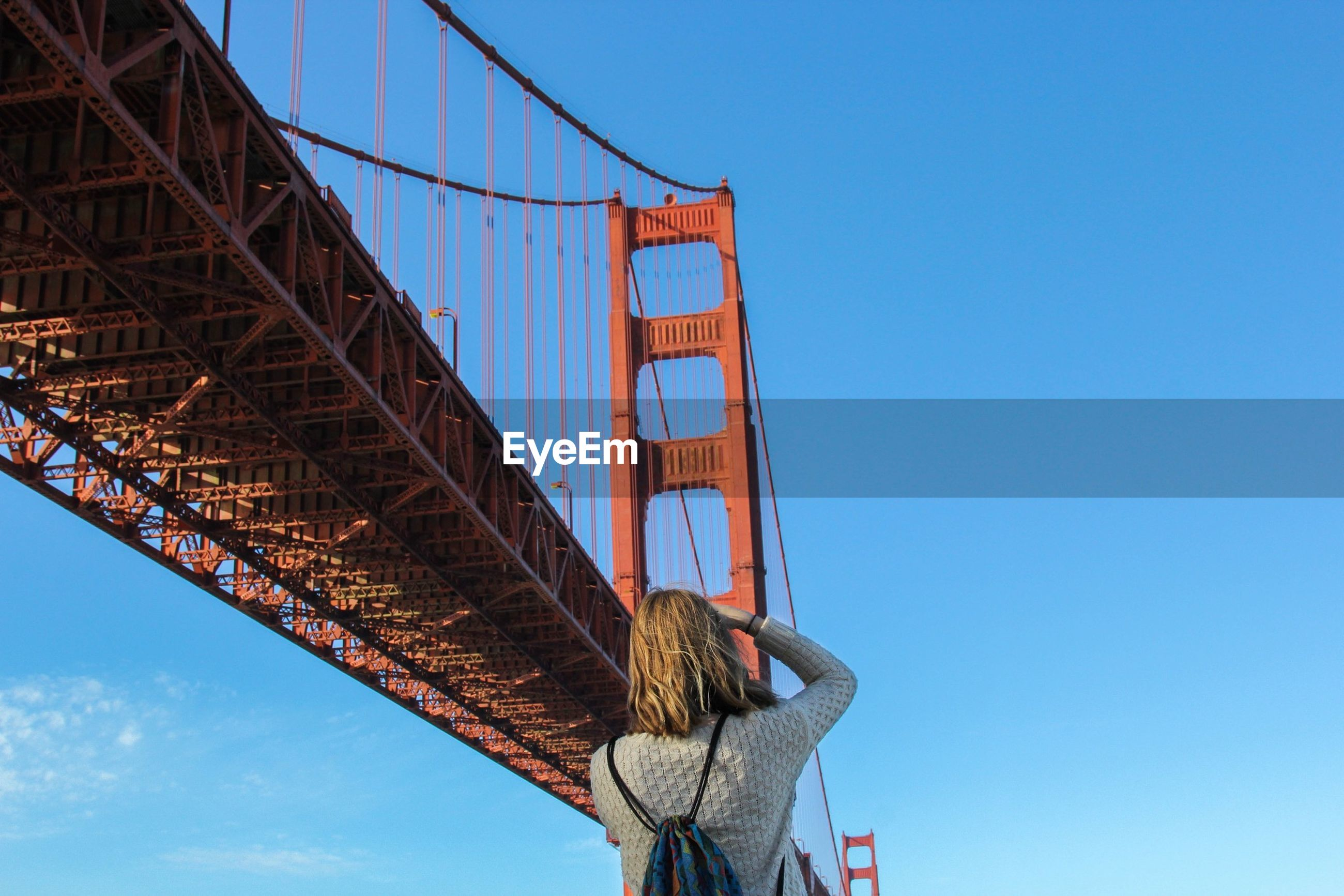 Rear view of woman photographing golden gate bridge against sky