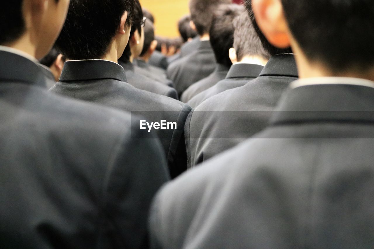 Rear view of young men in suits at ceremony