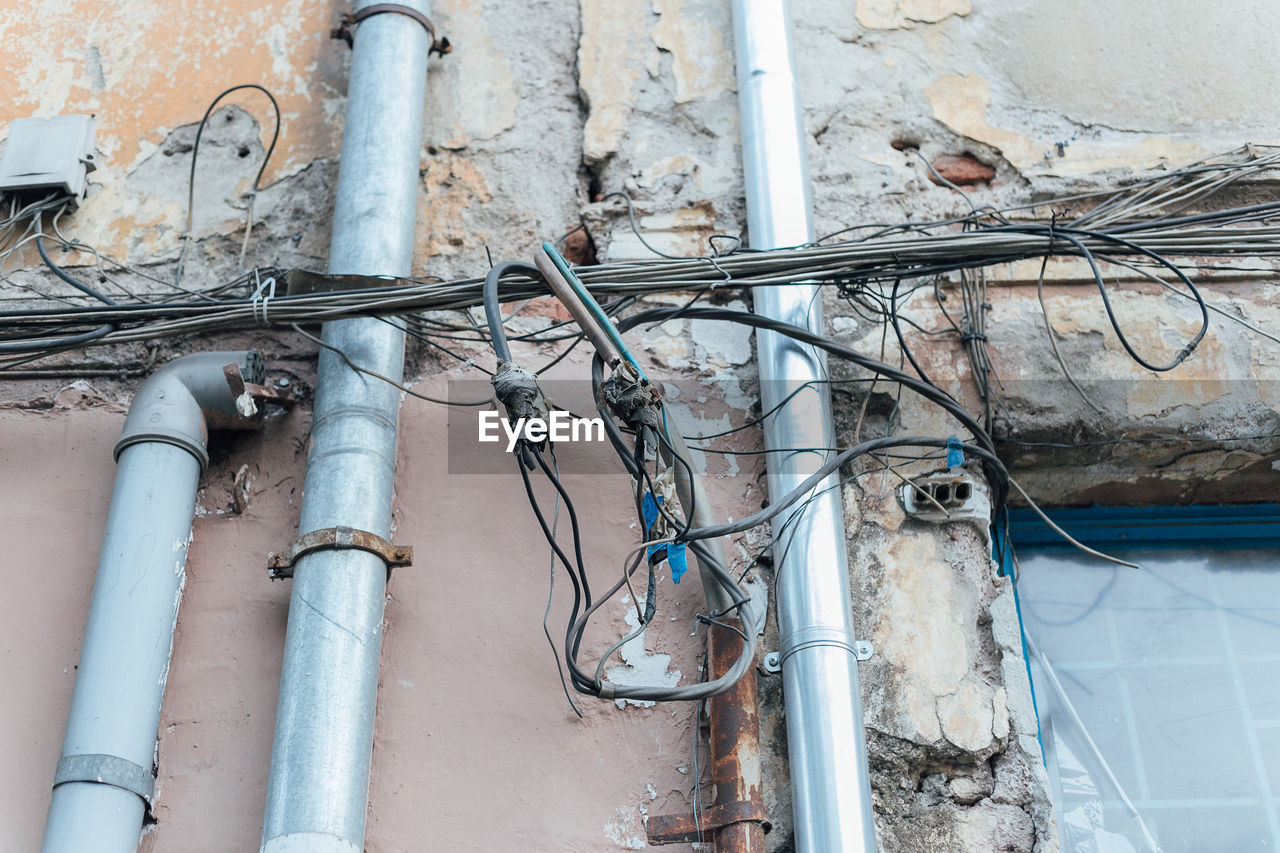 pipe - tube, no people, architecture, metal, built structure, cable, fuel and power generation, connection, day, electricity, wall - building feature, pipeline, building exterior, pipe, technology, power supply, wire, power line, outdoors, low angle view