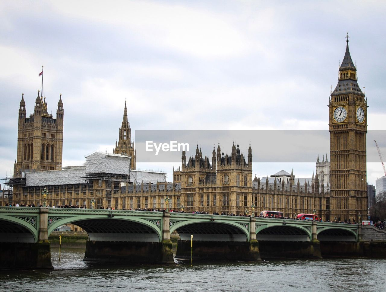 architecture, water, river, built structure, tower, clock tower, bridge - man made structure, building exterior, connection, travel destinations, waterfront, cloud - sky, sky, day, no people, city, outdoors