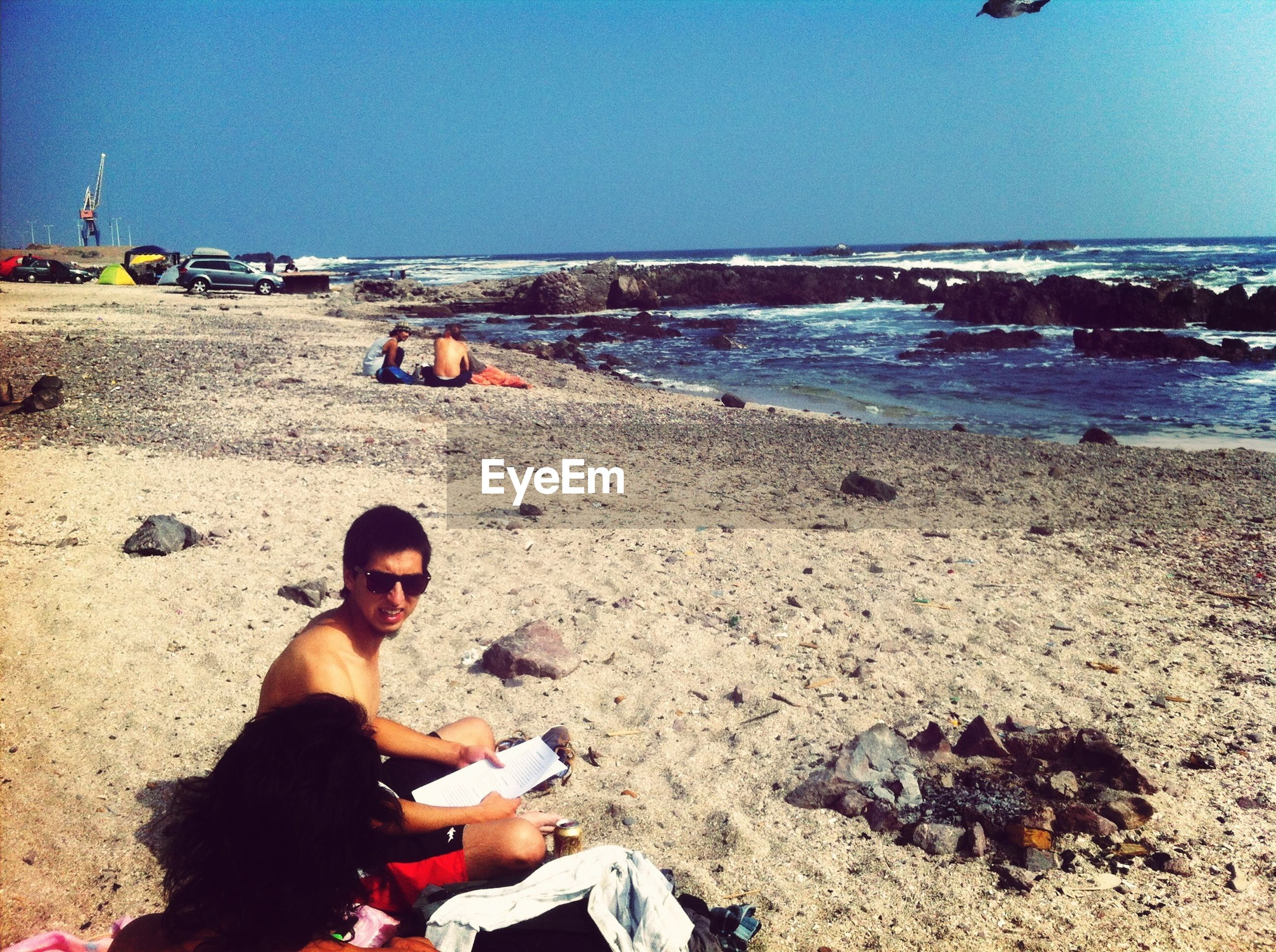 beach, sea, sand, shore, clear sky, leisure activity, lifestyles, water, horizon over water, copy space, sky, sunlight, rear view, men, vacations, casual clothing, sitting, incidental people