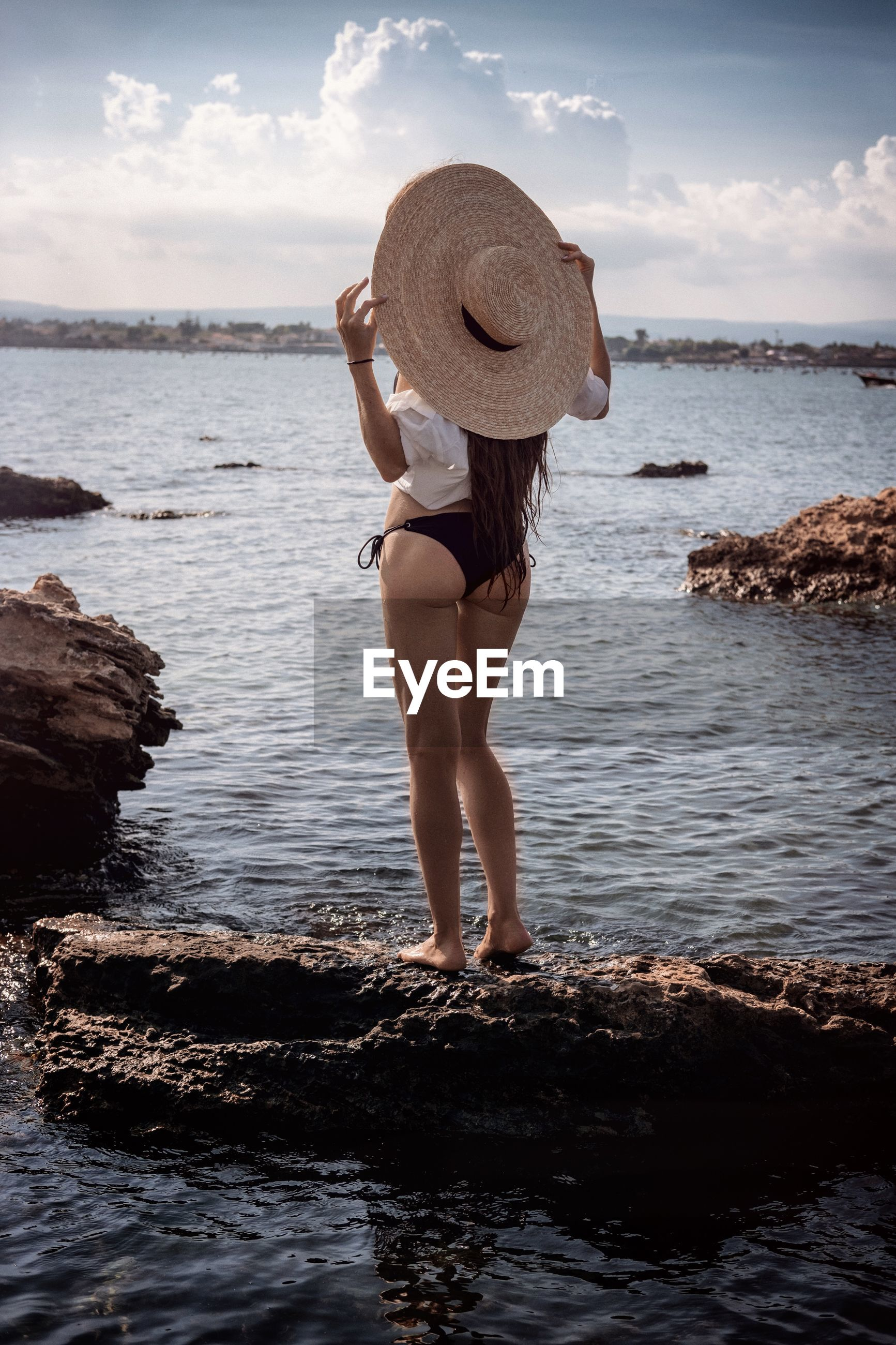 Rear view of woman wearing hat while standing on rock at beach against sky